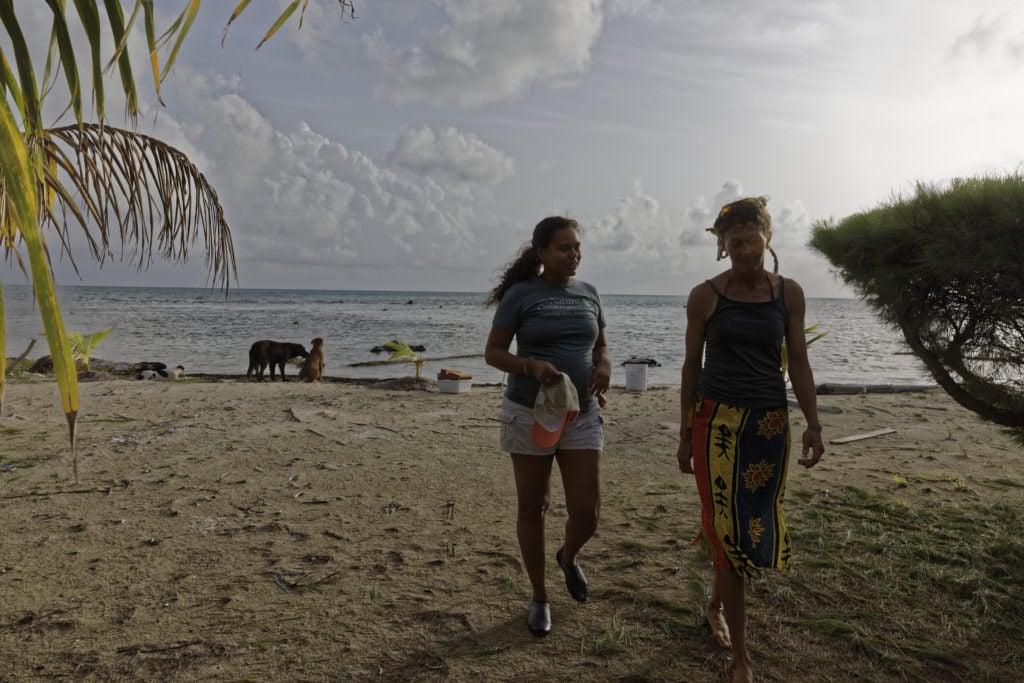 Julie Robinson walks on a beach near a seaweed farm
